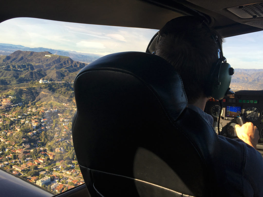 ethan in the cockpit looking out at griffith observatory and the hollywood sign