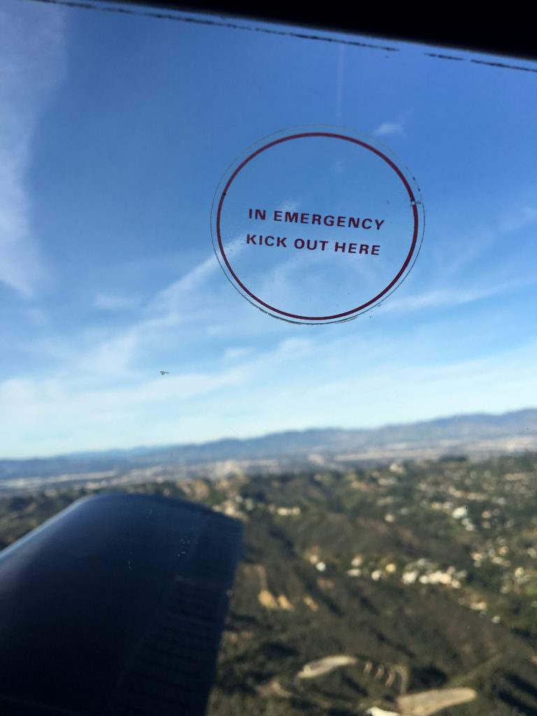 "close up on the ""in emergency kick out here"" window sticker"